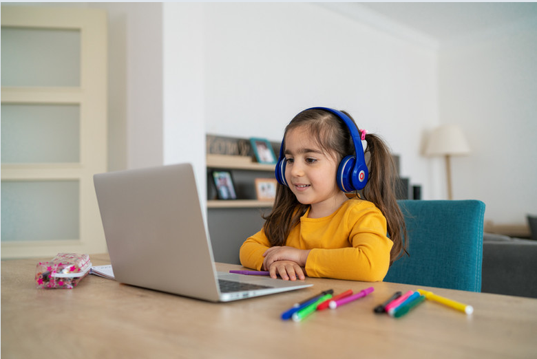 Hispanic girl learning at home with headphones copy