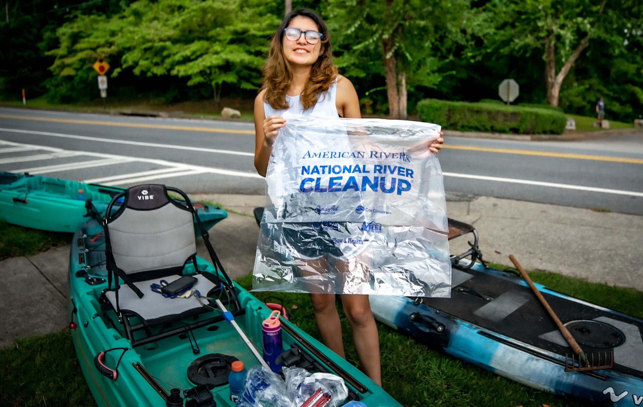 Smiling cleanup volunteer with bag and kayak