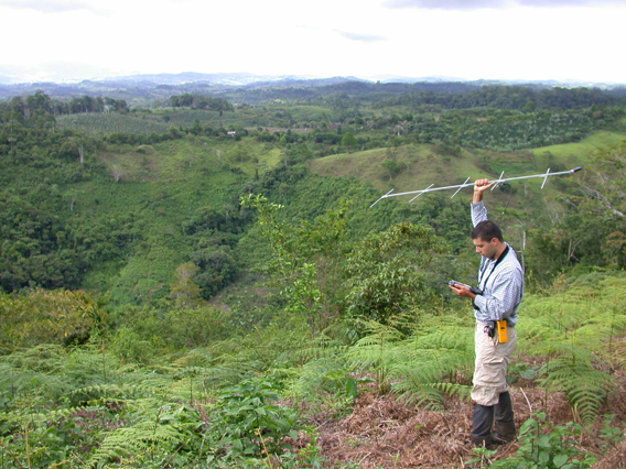 Çağan Şekercioğlu uses radio equipment to track an orange-billed nightingale-thrush in the Costa Rican countryside. A new study by Şekercioğlu indicates that wooded 'shade' plantations where coffee and cacao are grown are better for bird diversity than open farmlands, although forests still are the best habitat for tropical birds. Photo by: Mauricio Paniagua Castro.