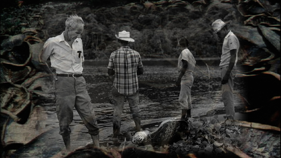 Archer Carr (far left) surveys a turtle killed for its meat. Photo courtesy of Two Head Productions.