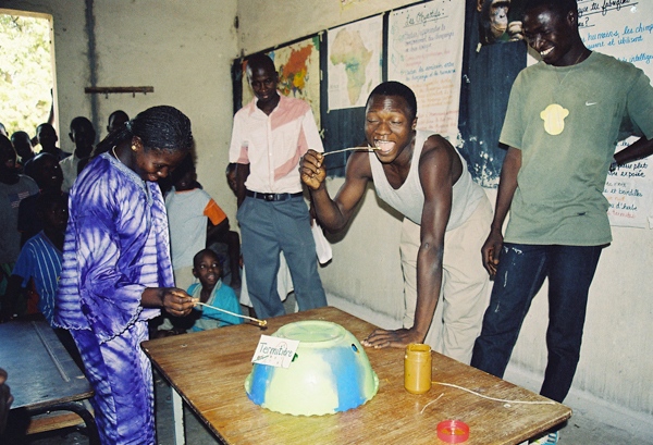 Dondo-Kante (far right) PEN's-December Educator of the Month at one of Amy Clanin's chimpanzee workshops in Senegal, teaching students how to 'fish-for-termites' using peanut butter and raisins. Photo by: Amy Clanin.