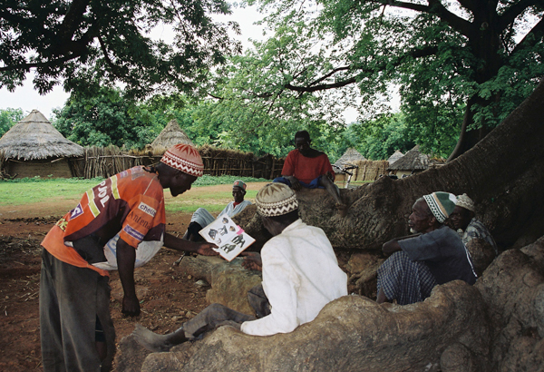 Villagers sharing a book on great apes following Amy Clanin's workshop on chimpanzees in Senegal. Photo by: Amy Clanin.