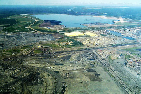 Aerial view of Syncrude's base mine with tailing pond in the background. Photo in Public Domain.