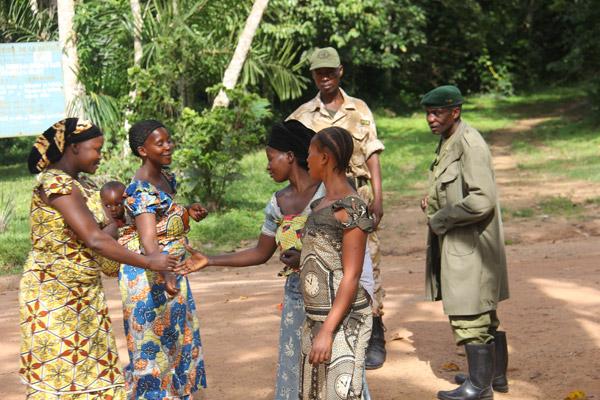 Personnes se saluant à un poste de contrôle à Epulu. Photo gracieusement autorisée par le Projet de Conservation de l'Okapi.