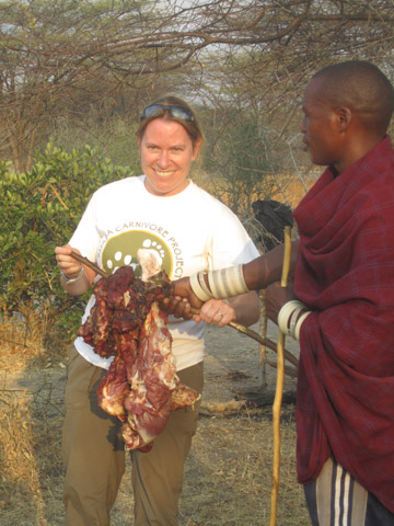 Amy, a staunch vegetarian, accepts a gift of meat from a Barabaig warrior. This was the first time that the Barabaig had invited RCP to one of their gatherings, so was a breakthrough moment for the project. Photo by: © Ruaha Carnivore Project.
