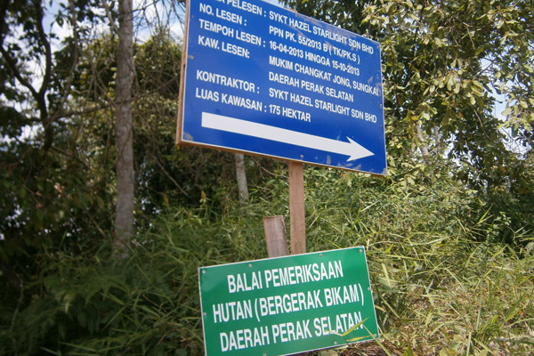 Sign on the bottom for Bikam Forest Reserve. Top sign relates to companies clearing the forest. Photo by: Meorrazak Meorabdulrahman.