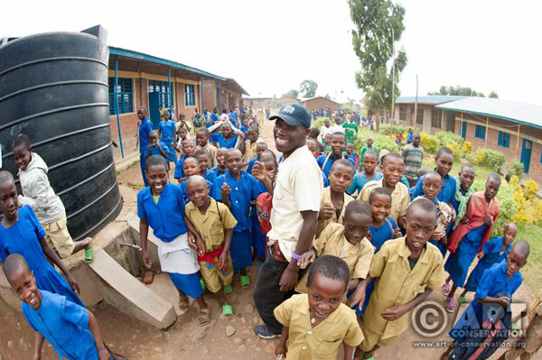 AoC worker, Innocent, at Nyange School with children. AoC gifted Nyange School with three 10,000 liter rain water tanks. Photo: © Andrew Walmsley.