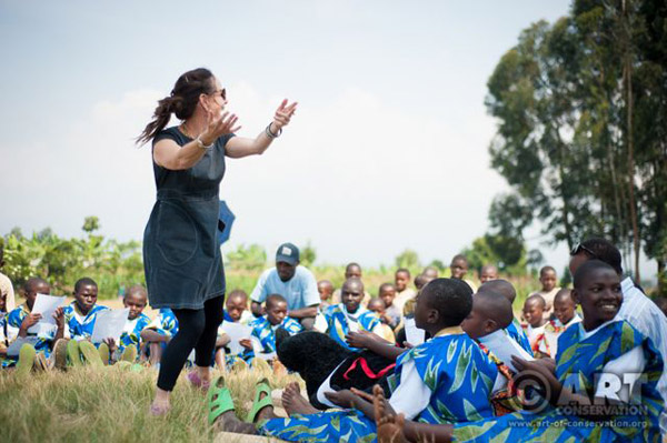 Ghrist (standing) with students (ages around 10 to 15) at Nyange School in Rwanda. Ghrist is choreographing a song called Mu Birunga (In Virunga) by Courtney Kaiser and Benjamin Kartel. The children were readying to perform these song and dances at Igitaramo (community party) the day before Rwanda's annual gorilla naming ceremony. Photo by: Andrew Walmsley.