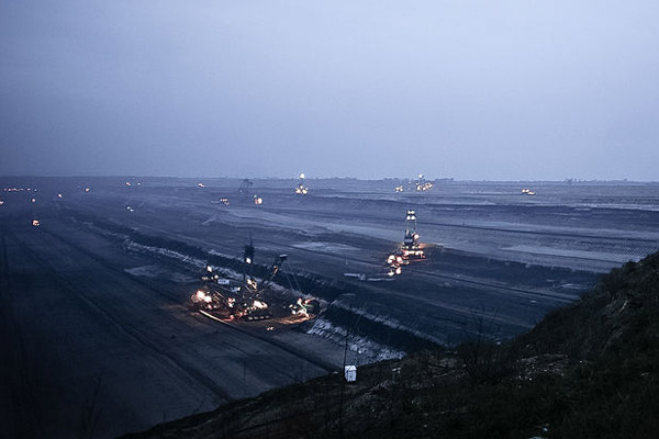 Vehicles work at night in the Tagebau Garzweiler coal surface mine in Germany. Photo by: CherryX.
