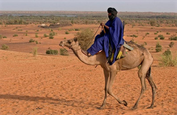 Mali is a melting pot of human diversity. Here a Tuareg rides a camel with Lake Banzena in the background. Photo by: Carlton Ward Jr.