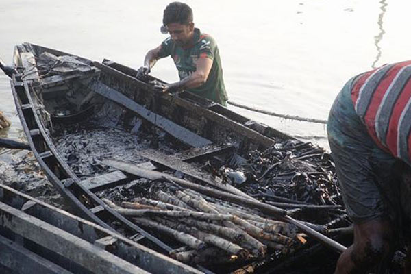 Locals land with a boat full of collected oil as well as branches coated in oil. The state-owned Padma Oil Company is paying locals for all the oil brought in. Photo by: Kallol Mustafa.