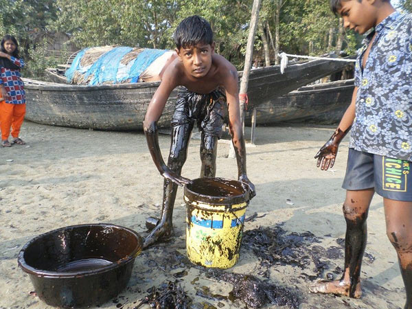 Government inaction has pushed local children and families to attempt to clean up the oil spill with little more than household items and no protective gear. Photo by: Kallol Mustafa.