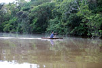 Indigenous Tikuna paddling a dugout canoe on a tributary of the Amazon [colombia_1162]