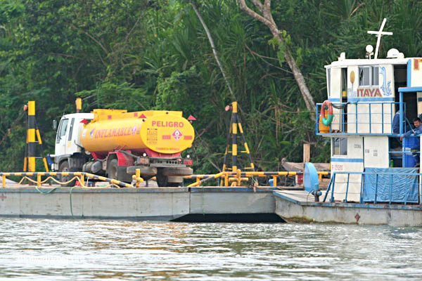 Oil truck being transported on the Napo River in the Ecuadorian Amazon; side of truck reads: INFLAMABLE