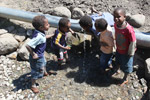Papuan kids drinking out of a leaking water pipe [papua_5115]