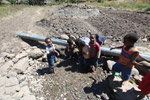 Papuan kids drinking out of a leaking water pipe [papua_5116]