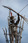 Dani elder in traditional dress with a bow and arrow atop a watch tower [papua_5401]