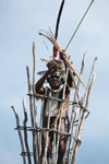 Dani elder in traditional dress with a bow and arrow atop a watch tower [papua_5409]