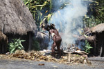 Papuan man roasting hog [papua_5788]