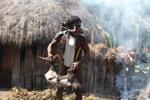 Dani man roasting a pig [papua_5818]
