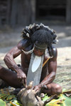 Dani man cutting into a roast pig using a bamboo knife [papua_5861]