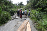 Papuans reparing a hole in the road using boards