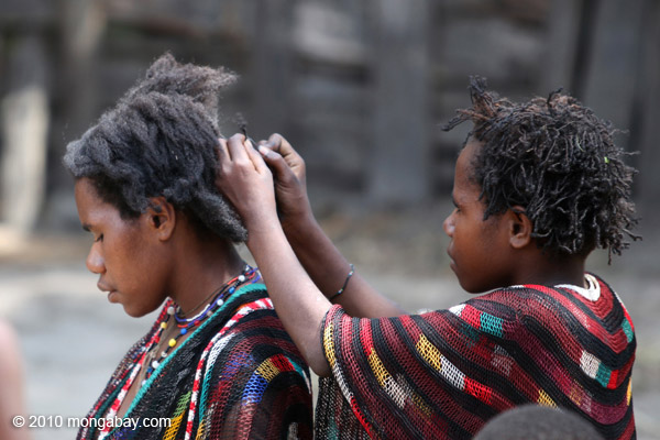 Papuan girl doing another's hair [papua_5855]