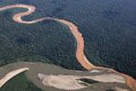 Muddy, mine waste-laden stream flowing into a rainforest river