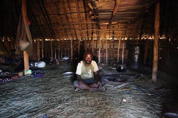 Lani-Stammesangehöriger in seiner Hütte