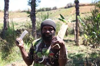 Hombre Lani cargando leña y un machete