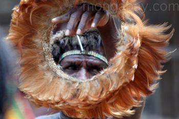 Ein papuanischer Mann hält einen Federkopfschmuck