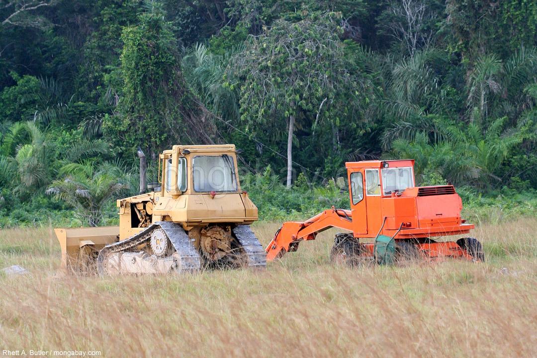 Traktoren nahe bei einem Stück Regenwald