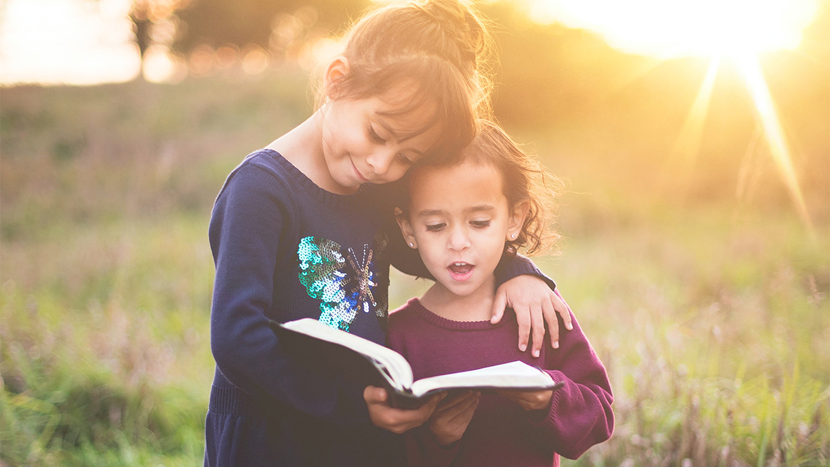 photo: two girls reading a Bible