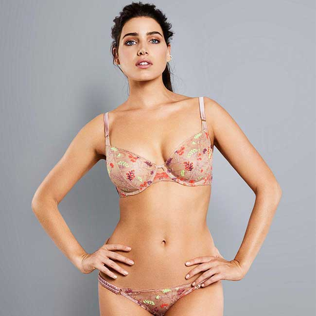 Model wearing colorfully embroidered nude bra and underwear.