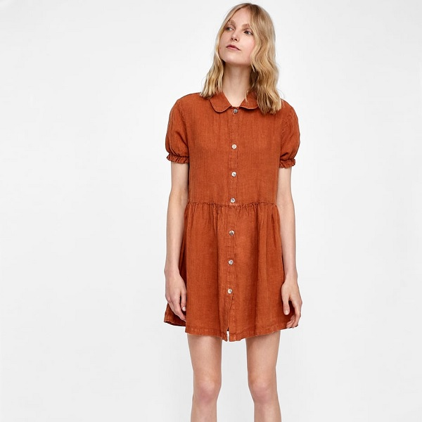 woman wearing a burnt orange button front dress with peter pan collar