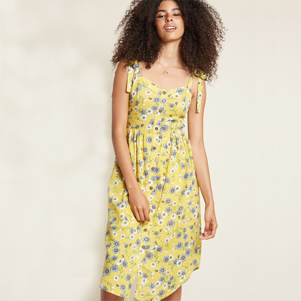 woman wearing yellow button front dress in floral print