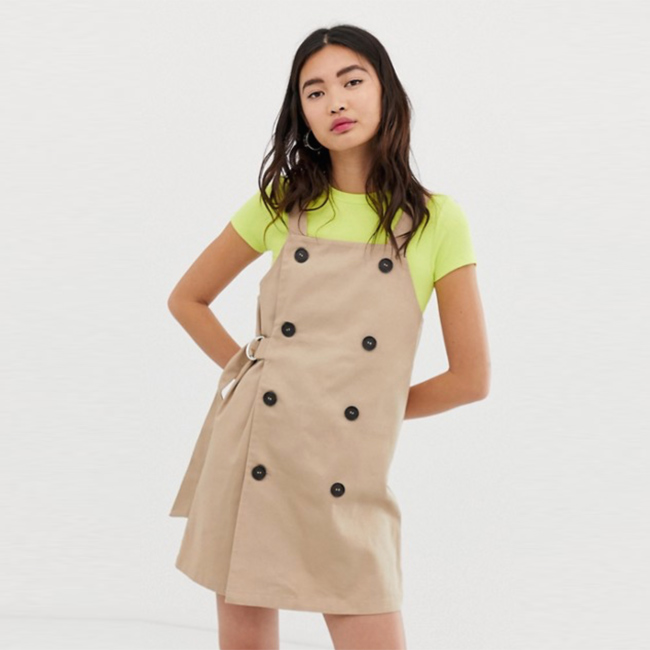 Model wearing tan trench coat-style overall dress with belt over neon yellow short-sleeve t-shirt