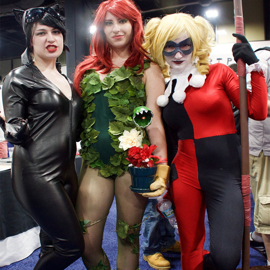 Women wearing Cat Woman, Poison Ivy, and Harley Quinn comic book costumes