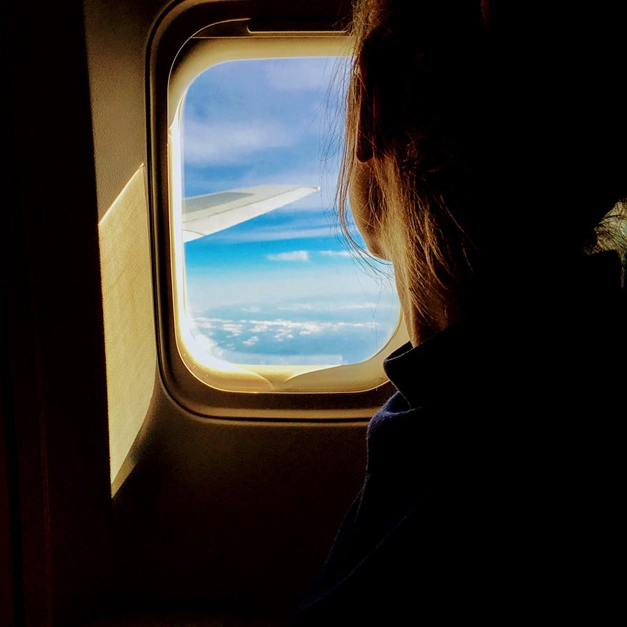 woman looking out of an airplane window
