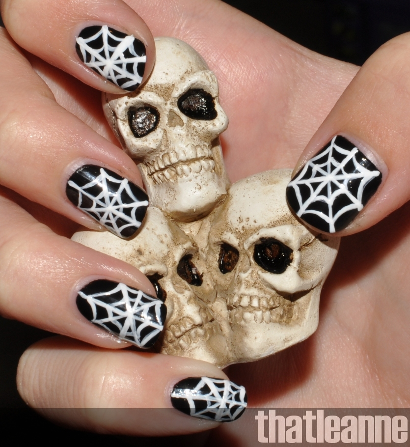 halloween nails with black polish and white spiderwebs