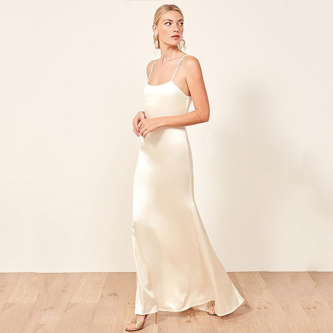 Floor-length ivory slip dress with slight scooped neckline and open back with spaghetti straps