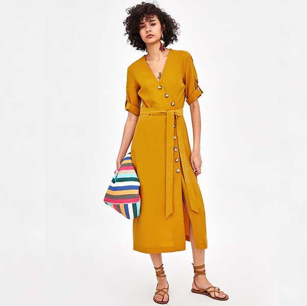 woman wearing button front dress in mustard color with a belt