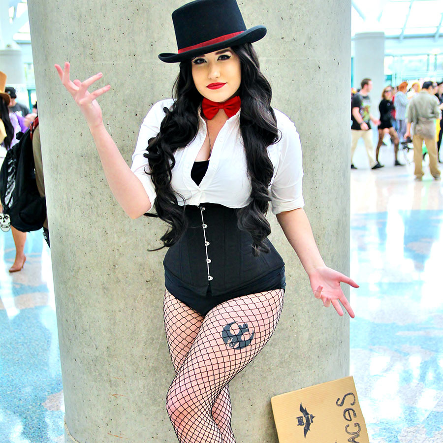 Woman wearing Zatanna comic book costume, complete with black top hat, white button up shirt, and black fishnet tights