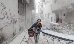 A boy carries his belongings at a site hit by what activists said was a barrel bomb dropped by forces loyal to Syria's President Bashar al-Assad in Aleppo's al-Fardous district