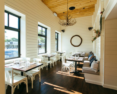 Wilkus Architect's project featuring wood paneling and custom restaurant seating