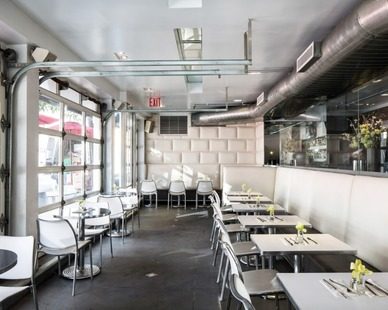 Kimberly Peck Architect created this restaurant design with an industrial feel with the concrete floors and exposed ceiling and walls and industrial restaurant seating options