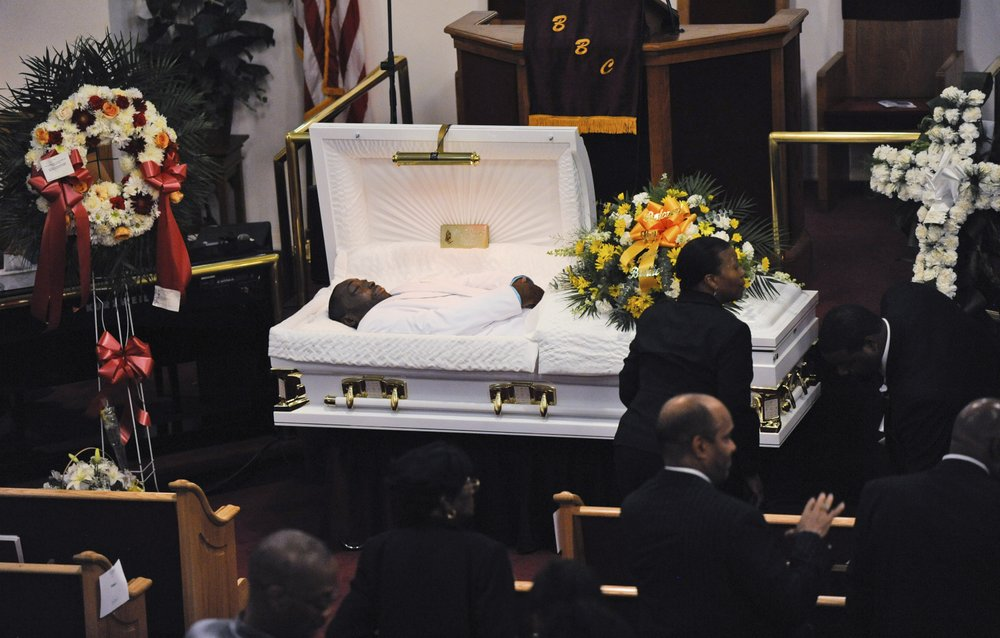 "FILE - In this July 23, 2014 file photo, Eric Garner's body lies in a casket during his funeral at Bethel Baptist Church in the Brooklyn borough of New York. On Friday, Aug. 2, 2019, an administrative judge recommended firing a New York City police officer Daniel Pantaleo, who is white, over the chokehold death of the unarmed Garner, whose dying cries of ""I can't breathe"" fueled a national debate over policing, race and the use of force. (AP Photo/New York Daily News, Julia Xanthos, Pool)"