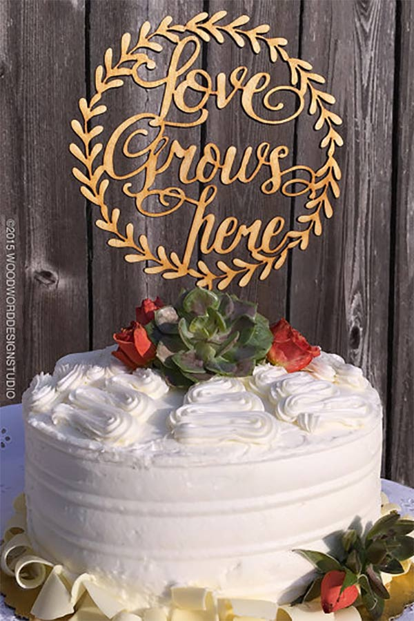 """This rustic love cake topper declares, """"Love Grows Here."""" Very cute for a country barn wedding. I like that it's wooden. Looks more authentic. #MyOnlineWeddingHelp #RusticWedding #CakeTopper #WeddingCake #BarnWedding"""