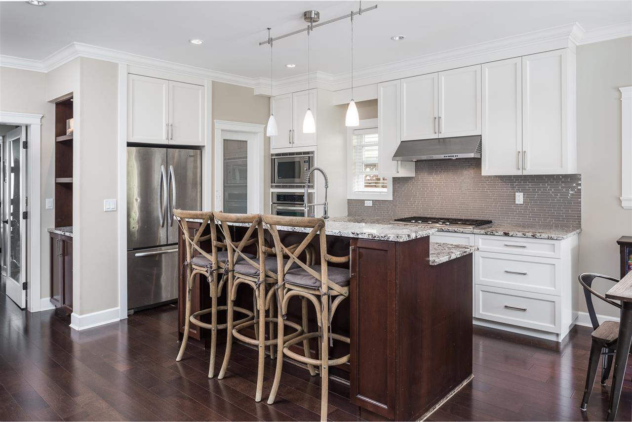 A Chef's kitchen! It has SS appliances, gas stove, granite counters, large island, shaker style cabinets, and the best part.....a Pantry!!!  It has a separate nook/eating area, overlooking the fam/dining area.  French doors off the kitchen lead to patio.
