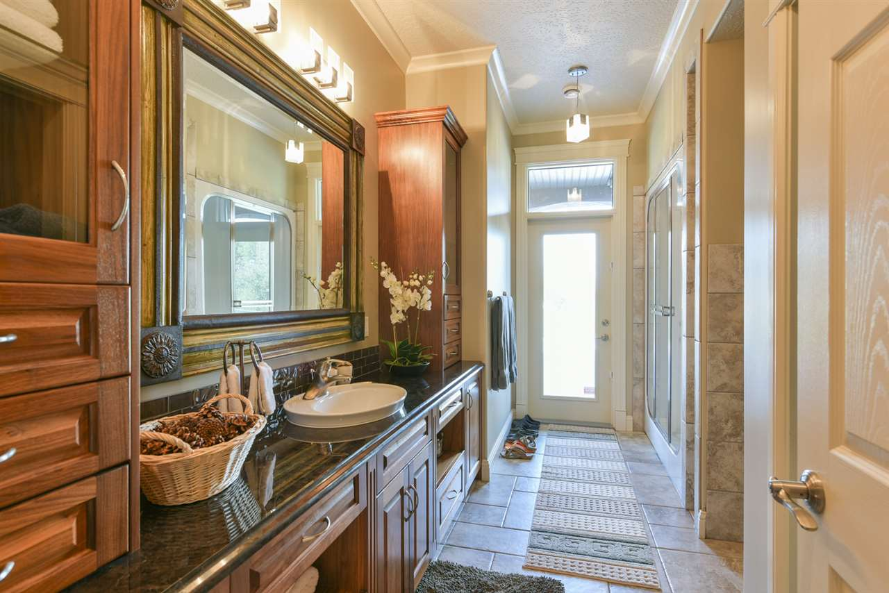 Just steps from the hot tub on the lower patio this beautiful bathroom features a Steam Unit, urinal, bathroom facilities and rich built in cabinetry and tile flooring!